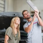 Auto repair shop series: In this photo, the male mechanic and female client look at the car's air filter and discuss the work that should be performed.