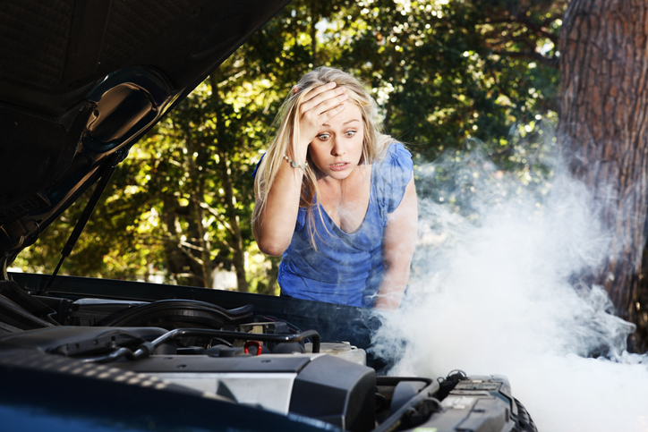 This pretty blonde girl, stranded after a car breakdown, looks down at her smoking car engine, hand to her head in horrified confusion and frustration.