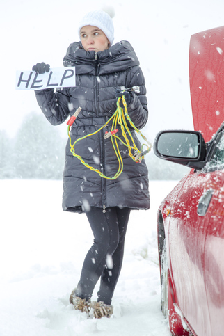 Cute woman driverl waiting for help on the road, she needs a battery boost for her car on very snowy winter day. Holding HELP sign.